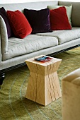 Solid wooden designer stool in front of light grey sofa with velvet cushions in various shades of red