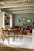 Antique dining table and wooden chairs in living-dining room of country house with rustic beamed ceiling