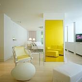Weisses Hotelzimmer mit postmodernem Interieur - Sitzgruppe mit Sessel, Deko-Ei und klassischer Polstergarnitur als Reflektion im gelb getönten Spiegel
