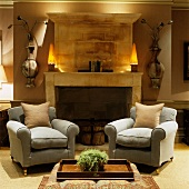 Comfortable reading chairs in front of open fireplace and vase-like ornaments on wall next to lamps on mantelpiece in traditional living room