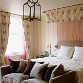 Scatter cushions on sofa at foot of double bed with canopy in traditional bedroom