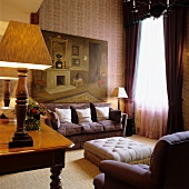 Grand salon with upholstered sofa and ottoman in front of window and table lamp on antique desk