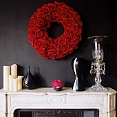 Candles and vases on white stone mantelpiece and wreath of red roses on black wall