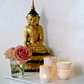 Lit candle lanterns next to roses in glass and gilt Buddha figurine on shelf