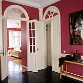 Foyer with walls painted dusky pink and view into living room through tall interior door with glass panels and arched transom window