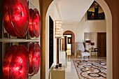 Wall lamp made of red discs in anteroom with view through arched doorway into elegant foyer with patterned tiled floor