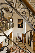 View of gallery and down into elegant foyer with patterned tiled floor through balustrade