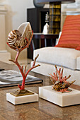 Decorative ornament made of coral and nautilus shell on table in front of pale sofa