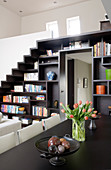 Custom-made staircase with integrated shelving leading to gallery; ornaments on Molteni dining table in foreground