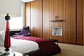 Designer bedroom with Italian furnishings and gas fire integrated into fitted wardrobe