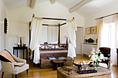 Colonial-style four-poster bed with curtains and wicker trunks in country house bedroom