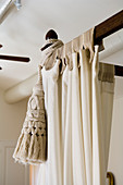 Skilfully made curtains and cream tassel on dark wood four-poster frame