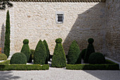 Topiary box bushes and hedges cut in various shapes on gravel surface against stone facade