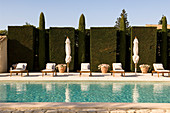 Row of wooden loungers and parasols in front of hedge beside swimming pool