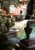 Lush, French garden with stone fountain and view of red house facade