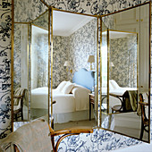 Traditional bedroom reflected in screen with integrated mirrored panels
