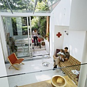Family in contemporary house - view from above down onto couch and classic side table in minimalist living room with access to garden