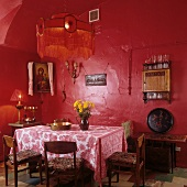 Simple dining room in red - table cloth on table below pendant lamp with fringed lampshade and red-painted walls