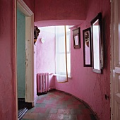 Pink, vintage corridor with curved wall and open door in period apartment
