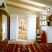 View across bed with ethnic bedspread to Oriental pointed archway and woman in hall