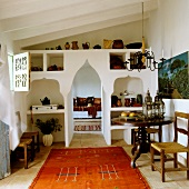 Ethnic rug in Mediterranean interior with pointed arched doorway