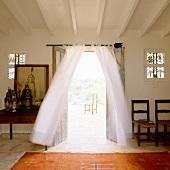 Folkloristischer Teppich vor offener Terrassentür mit luftigem Vorhang und Blick auf Stuhl in Freiem