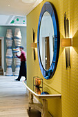 Round, wall-mounted mirror with blue frame between wall lamps on yellow, illuminated wall in open foyer with member of staff in background
