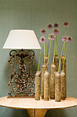 Group of ceramic vases holding single flowers and table lamp with white lampshade and vintage metal base on modern table against fabric-covered wall