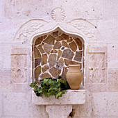 Jug and branches of leaves on masonry shelf in Oriental niche tiled with rough stone