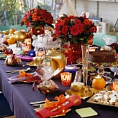 Festive coffee table set with bouquets, gilt crockery and tempting cakes and biscuits