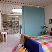 Colourful checked bed linen in bedroom and view through light blue sliding door into ensuite bathroom