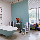 Maritime ensuite bathroom with director's chairs next to retro bathtub and view into loft apartment bedroom