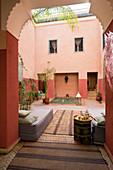 Blick durch hohes Tor in marokkanischen Innenhof auf Tagesbetten und Wasserbassin im Hintergrund