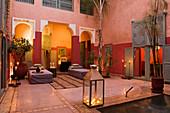 Kerzenlichtstimmung in marokkanischem Innenhof mit verschiedenen Rottönen an Wand