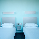 Twin beds with grey-painted headboards and wall lamps on blue wall in modern bedroom