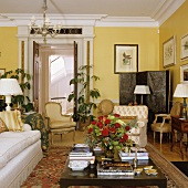 Grand living in room in yellow with sofa and antique armchairs around coffee table