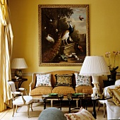 Table lamp with white fabric lampshade on small side table in front of Rococo bench and old painting on yellow-painted wall