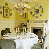 Festively set dinner table in front of open fireplace and decorative plates on yellow-painted walls