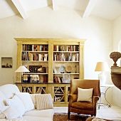 Bookcase, old leather armchair and sofa in living room of French country house