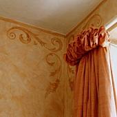 Zimmerecke mit Ornament-Muster an der Wand und Vorhang