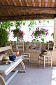 Simple wooden bench in front of Rococo-style chairs and masonry bench with cushions on veranda