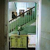 Rustic cabinet and rusty fridge in green and white stairwell; fresh flowers create a cheerful atmosphere