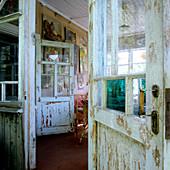 Abgeblätterte Farbe an alten Türen eines schlichten Holzhauses