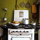 50er Jahre Herd in schlichter Küche, mit einem Teller frisch gebackener Pfannkuchen und einem Wasserkessel