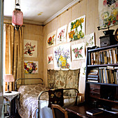 Simple bed in corner of room below cheerful, floral watercolours on wall