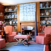 Corner of traditional living room - armchairs with checked loose covers and matching ottoman in front of fireplace flanked by shelves of decorative plates