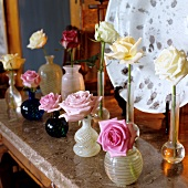 Single roses in different glass vases on stone slab