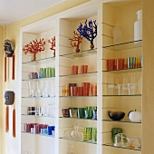Coloured drinking glasses on fitted shelving with glass shelves