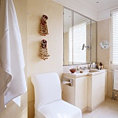 Pale, modern bathroom - chair with white loose cover next to washstand with base unit