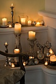 Various lit candles on candle sticks and holders in corner